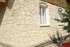 Облицовка фасада загородного дома камнем песчаником и известняком